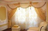 Шторы в классическом стиле в гостинной выполнены в молочно-золотистой гамме
