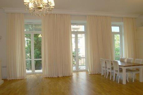 Однотонные шторы на больших окнах в зале выглядят нарядно и легко недорого