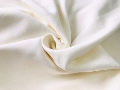 Однотонная плотная ткань молочного цвета