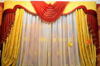 Контрастный ламбрекен выглядит нарядно на фоне штор золотистого цвета