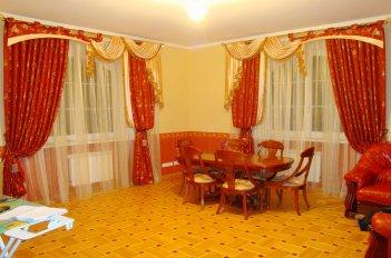Нарядные шторы с ламбрекеном в зале с двумя окнами