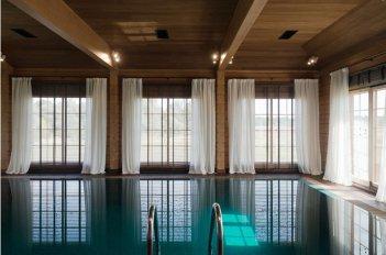 Окна в бассейне оформлены однотонными легкими шторами