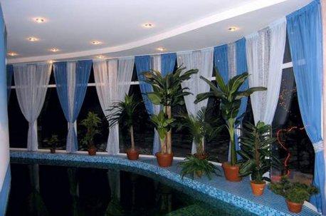 Сочетание голубого и белого цвета при оформлении окон в бассейне выглядит очень уместно недорого