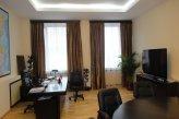 На двух окнах в кабинете висят ровные коричневые шторы