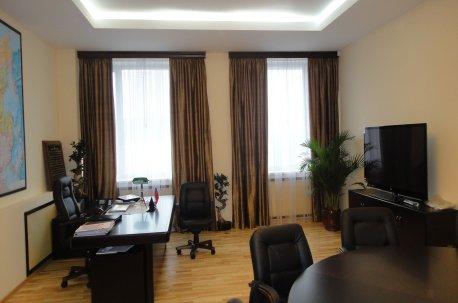На двух окнах в кабинете висят ровные коричневые шторы недорого