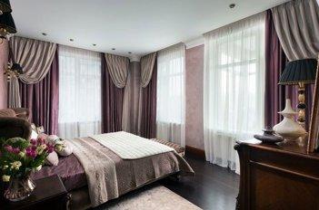 Большие окна в светлой спальне при необходимости зашториваются рабочими шторами