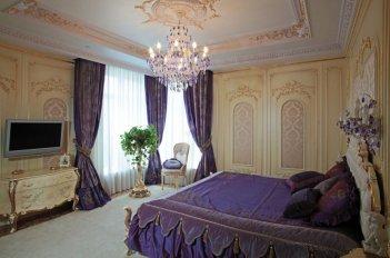 Сиреневые шторы в спальне выглядят эффектно на фоне стен персикового цвета