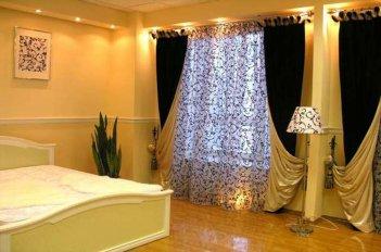 Шторы темного цвета со светлой подкладкой вносят нарядность в интерьер спальни