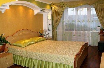 Комплект штор в спальне и покрывала, пошитый из одинаковых тканей выглядит уместно в спальне в классическом стиле