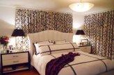Балдахин над кроватью и шторы на окне в спальне пошиты из одинаковых тканей