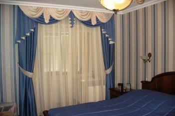 Шторы с ламбрекенами в бело-голубых тонах на окне в спальне
