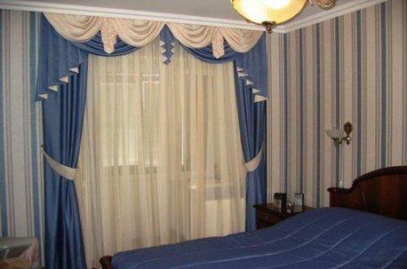 Шторы с ламбрекенами в бело-голубых тонах на окне в спальне недорого