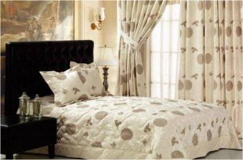 Шторы в спальне и покрывало выполнены из одинаковых тканей и смотрятся как гармоничный комплект