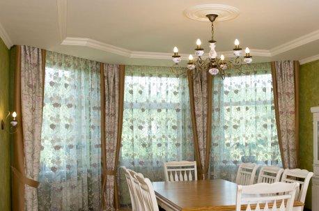 Гостиная - столовая с эркером украшена красивыми шторами недорого