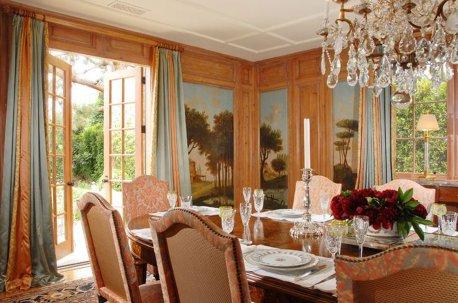 Шторы на окнах в гостиной - столовой, уложенные на пол, выглядят респектабельно даже при простом фасоне и однотонных тканях недорого