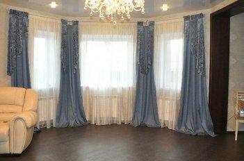 Шторы из голубого велюра на большом эркерном окне в гостинной