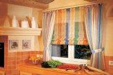 Сочетание римской шторы и легких декоративных штор на окне в столовой