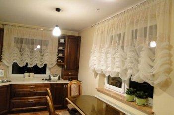 Легкие полупрозрачные гардины с французскими складками закрывают верхнюю часть окна