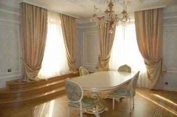 Большая светлая столовая-гостиная украшена нарядными шторами с подкладкой