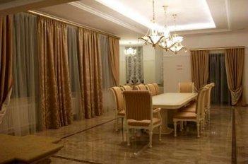 Золотистый цвет штор в гостиной гармонирует с текстильной оббивкой стульев