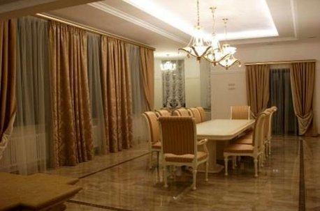 Золотистый цвет штор в гостиной гармонирует с текстильной оббивкой стульев недорого