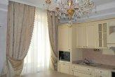 Цвет штор в гостиной удачно подобран по цвету к кухне