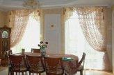 Ажурные занавески в ассиметричном фасоне на окнах в кухне-столовой